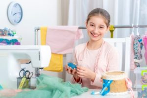 smiling girl while sewing