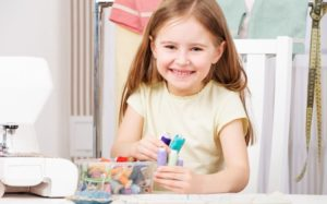 smiling kid with sewing tools